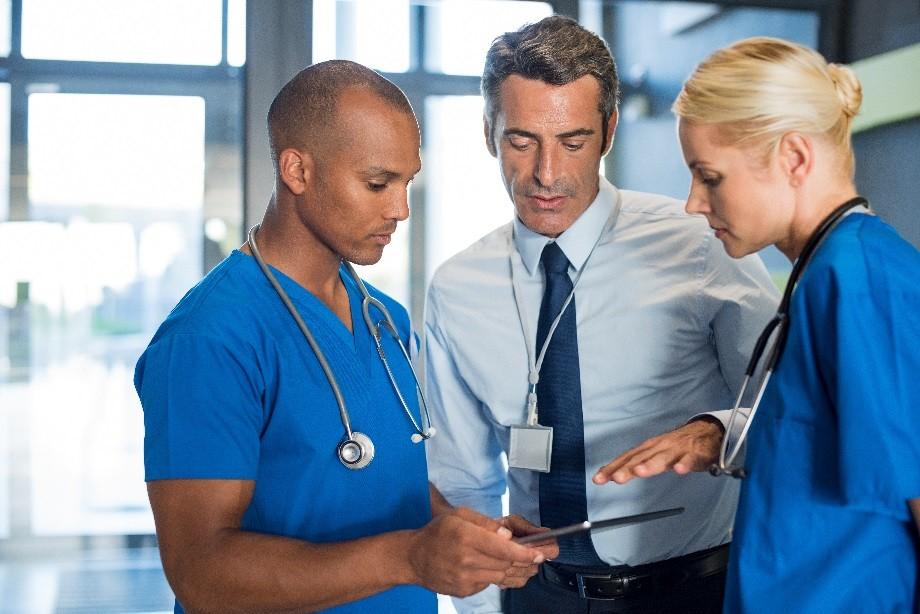 Medical team interacting using digital tablet at modern hospital.