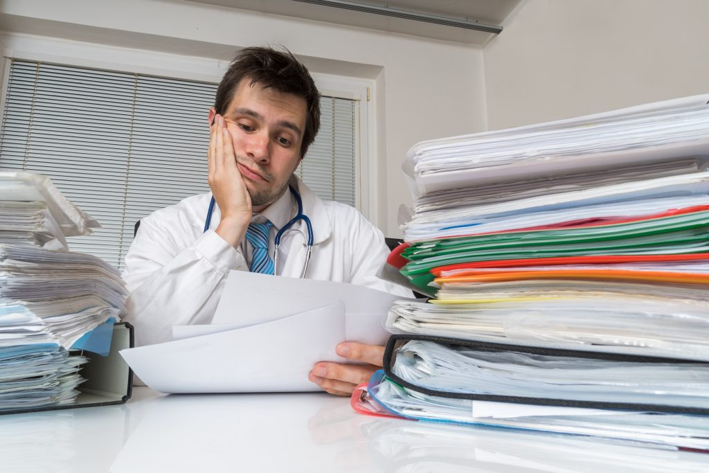Tired overworked doctor is reading medical report.