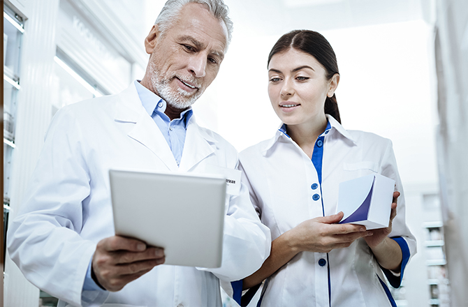 Doctor Showing Digital Tablet To Nurse In Hospital