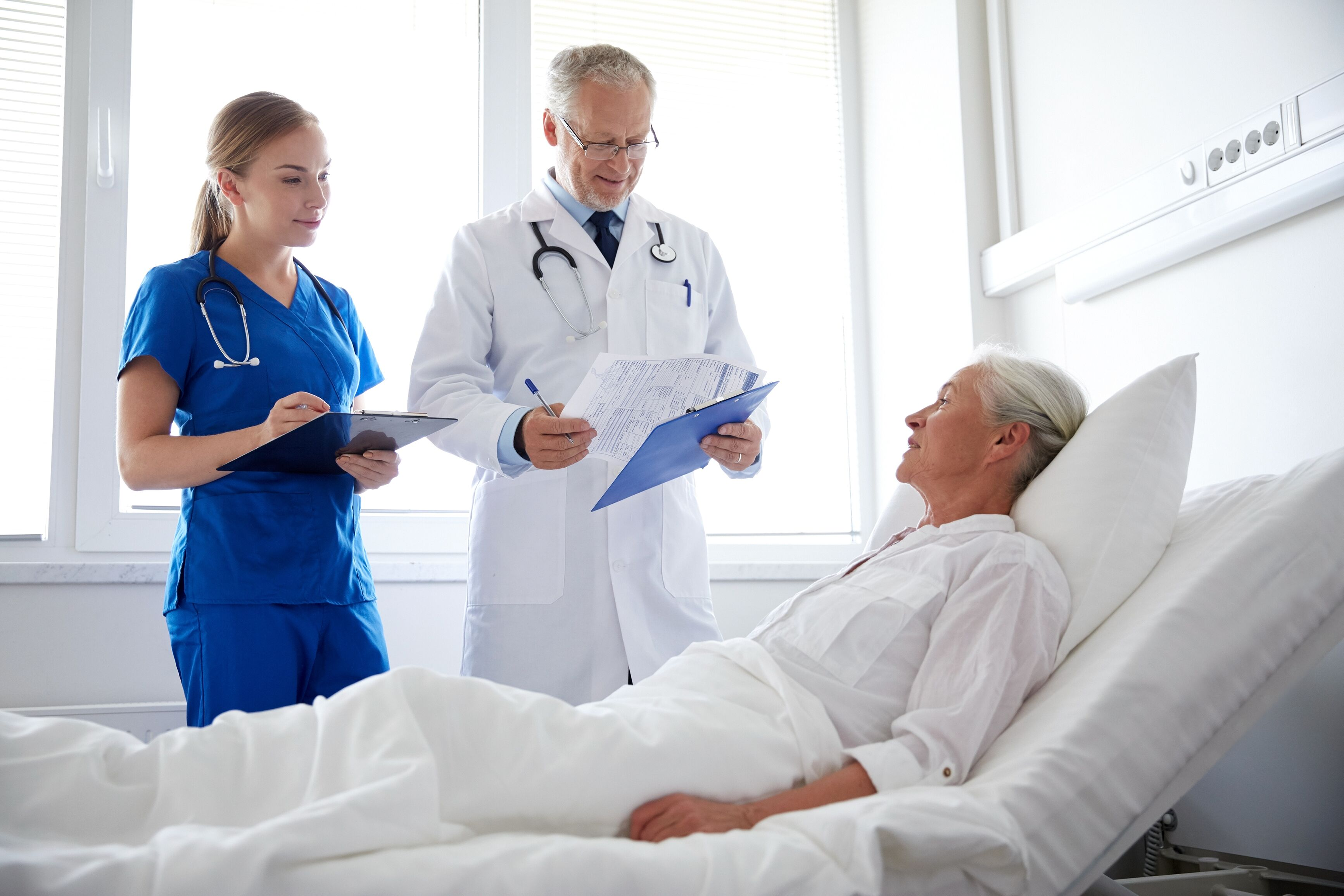 Doctor & nurse communicating with old patient