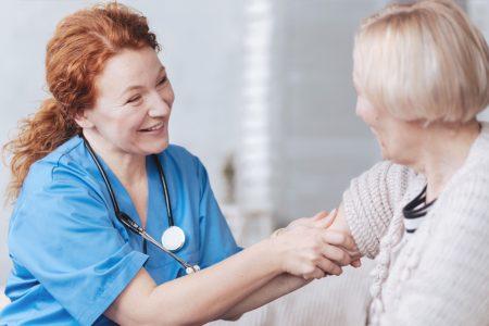 An elderly woman is talking with a nurse.