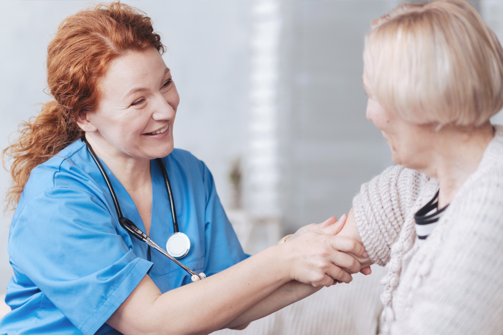 An elderly woman is talking with a nurse.