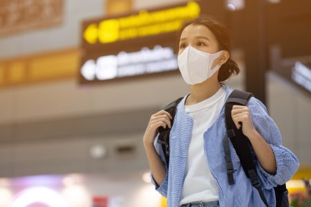 girl with medical face mask to protection the coronavirus in airport