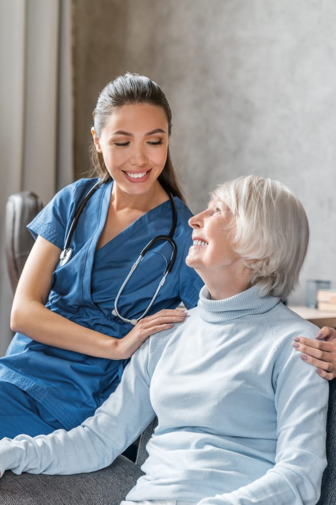happy elderly woman with nurse at home
