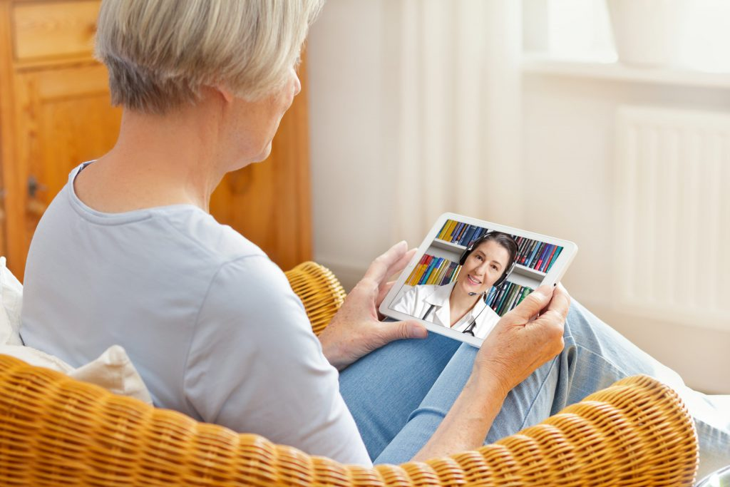 old woman with tablet pc during an online consultation with her doctor.