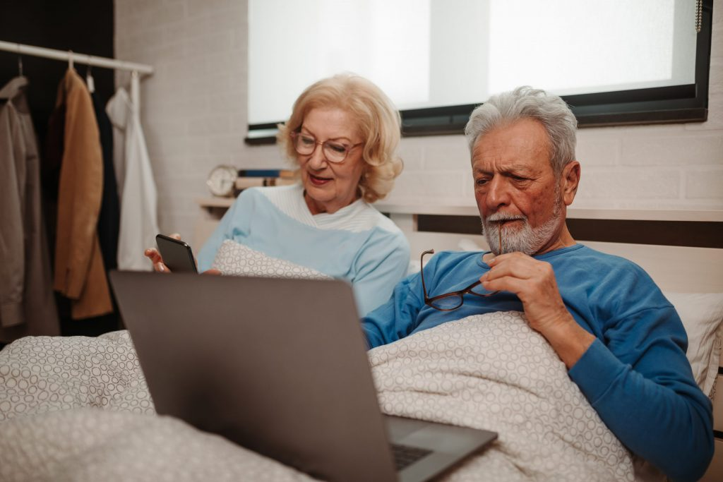 Elderly couple checking their mobile & laptop.