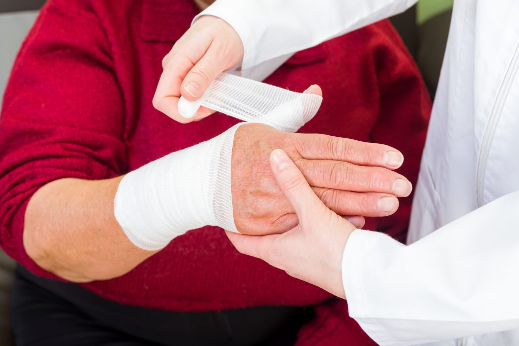 Nurse wrapping wounded hand