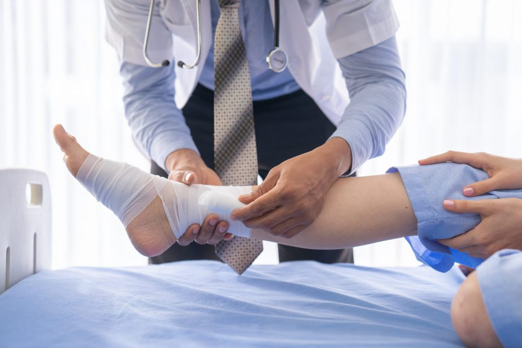 Physician wrapping wounded foot