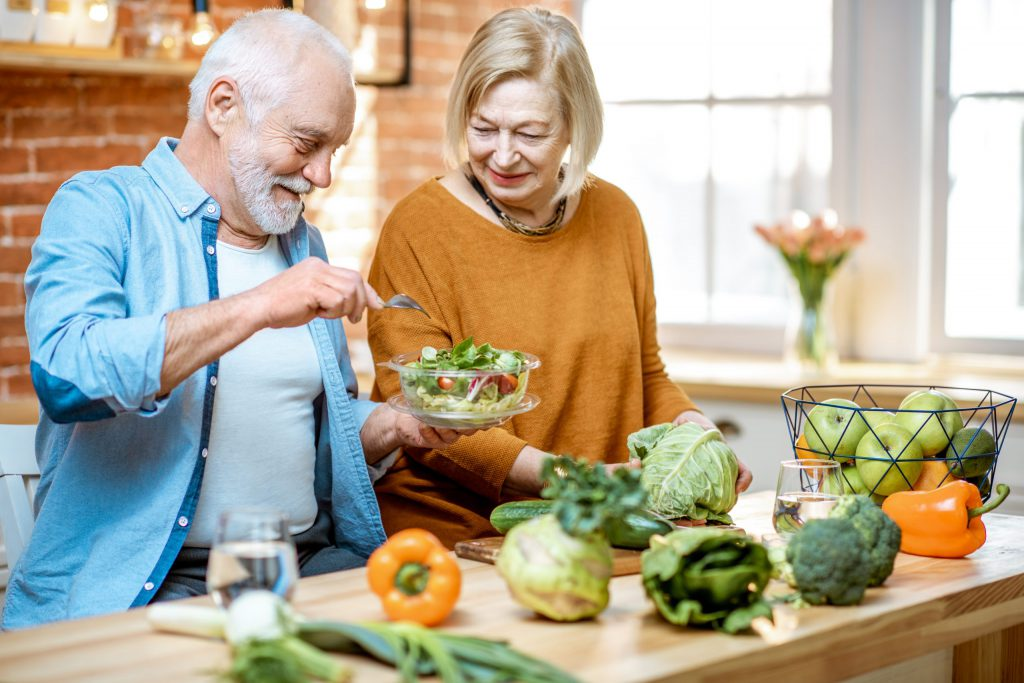 Couple having fun and preparing salad dish together