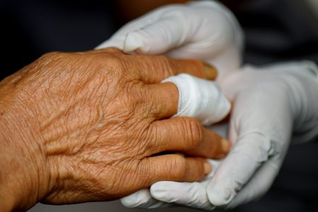 Nurse wrapping patient's wounded finger