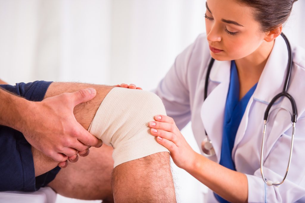 Nurse Applying Compression Wraps on patient's wounded leg