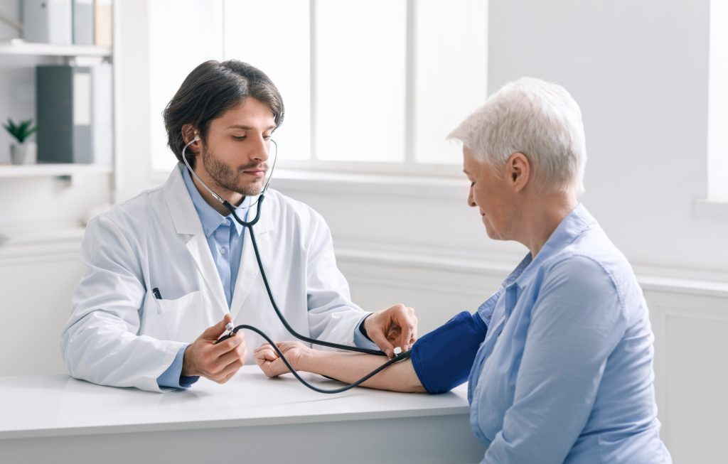 Physician Checking Patient's Blood Pressure