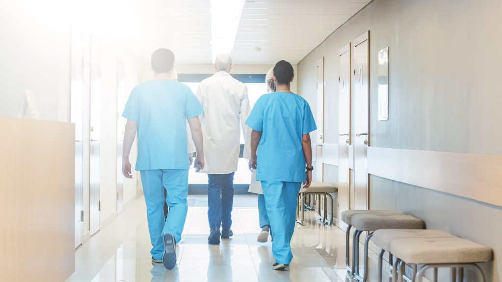 Group of Doctors Walking Through Hospital