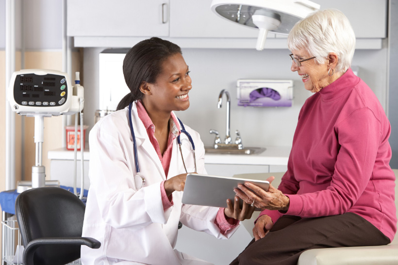 nurse happily showing something to patient in digital tablet